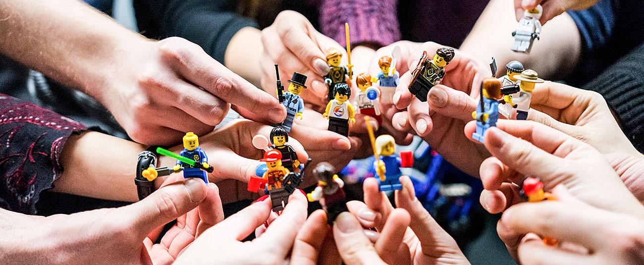 Hände halten Lego Serious Play-Figuren